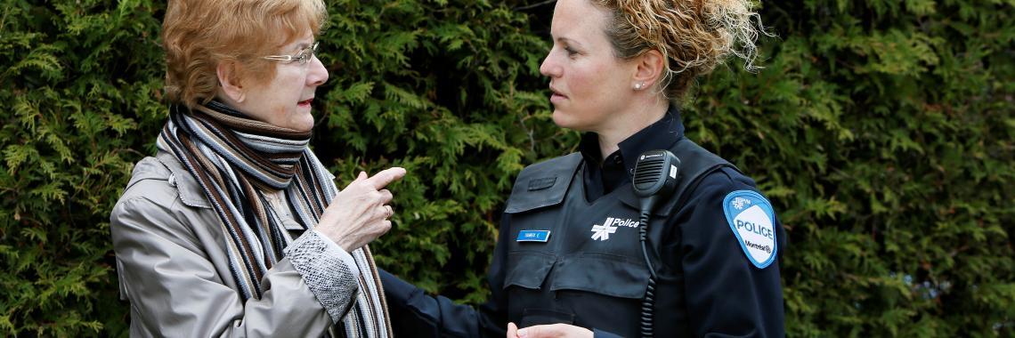 Policière discute avec une dame âgée